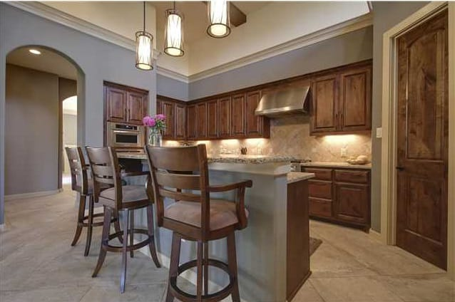 Kitchen with wooden cabinetry, granite countertops, cylindrical pendants, and a two-tier breakfast island.