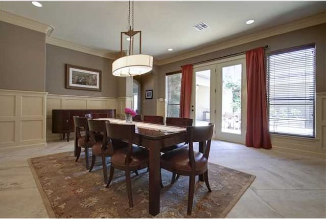 The dining room has a wooden buffet bar, a rectangular dining set, an oval chandelier, and a floral area rug.