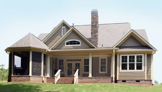 Rear exterior view showing the wide covered patio and turreted screened porch.
