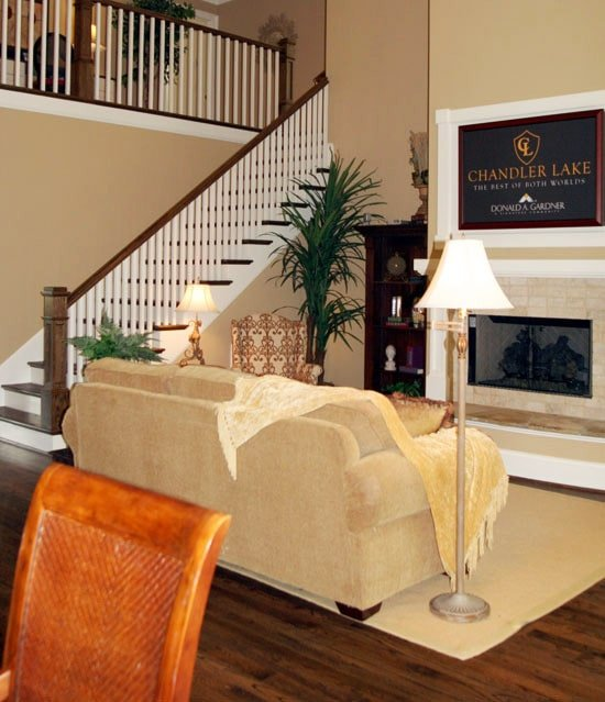 Living room with beige sectional, brass floor, and table lamps. brick fireplace, and fresh potted plants.