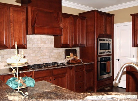 The kitchen is equipped with stainless steel appliances, granite countertops, redwood cabinets, and a curved peninsula.