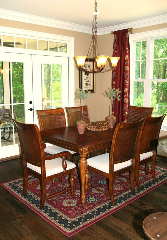 Dining room with a classic area rug, wooden dining set, warm glass chandelier, and a french door that leads out to the screened porch.