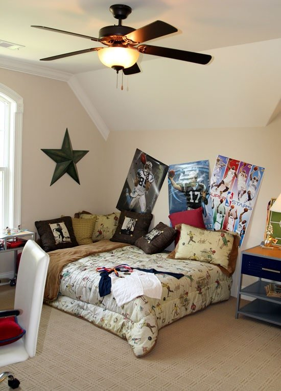 This bedroom has textured carpet flooring, vaulted ceiling, and beige walls adorned with sports posters.