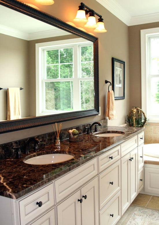 The primary bathroom is equipped with dual sink vanity and a deep soaking tub placed under the white framed window that's reflected in the large, rectangular mirror.