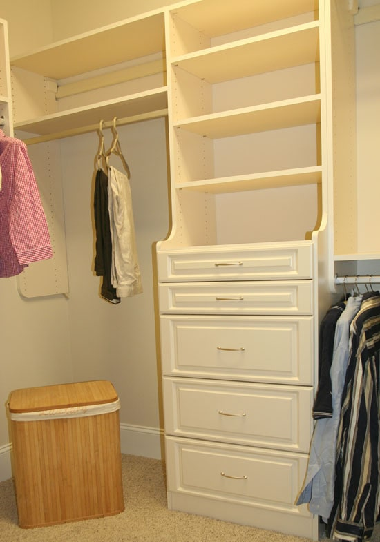 Walk-in closet with carpet flooring and built-in shelvings that blend in with the cream walls.