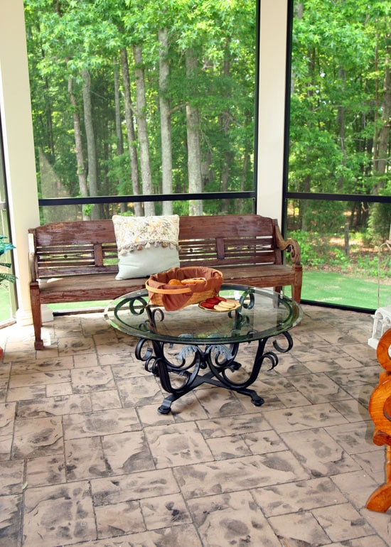 Screened porch with an ornate wrought iron table and a wooden bench accented by a classic pillow.