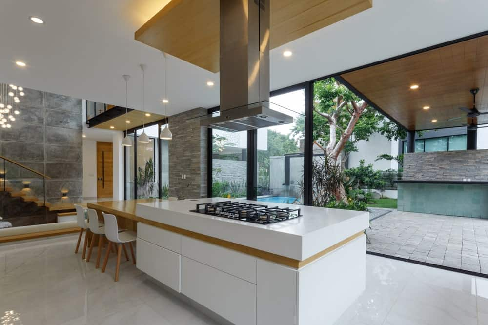 The cooking area of the kitchen is placed on its large kitchen island that has white cabinetry and white countertop topped with a stainless steel vent.