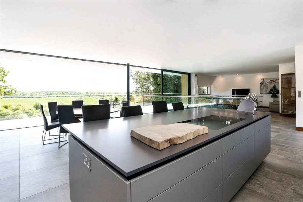 This is a view of the large great room from the vantage of the kitchen island with a dark countertop to match the dining area chairs on the far side.