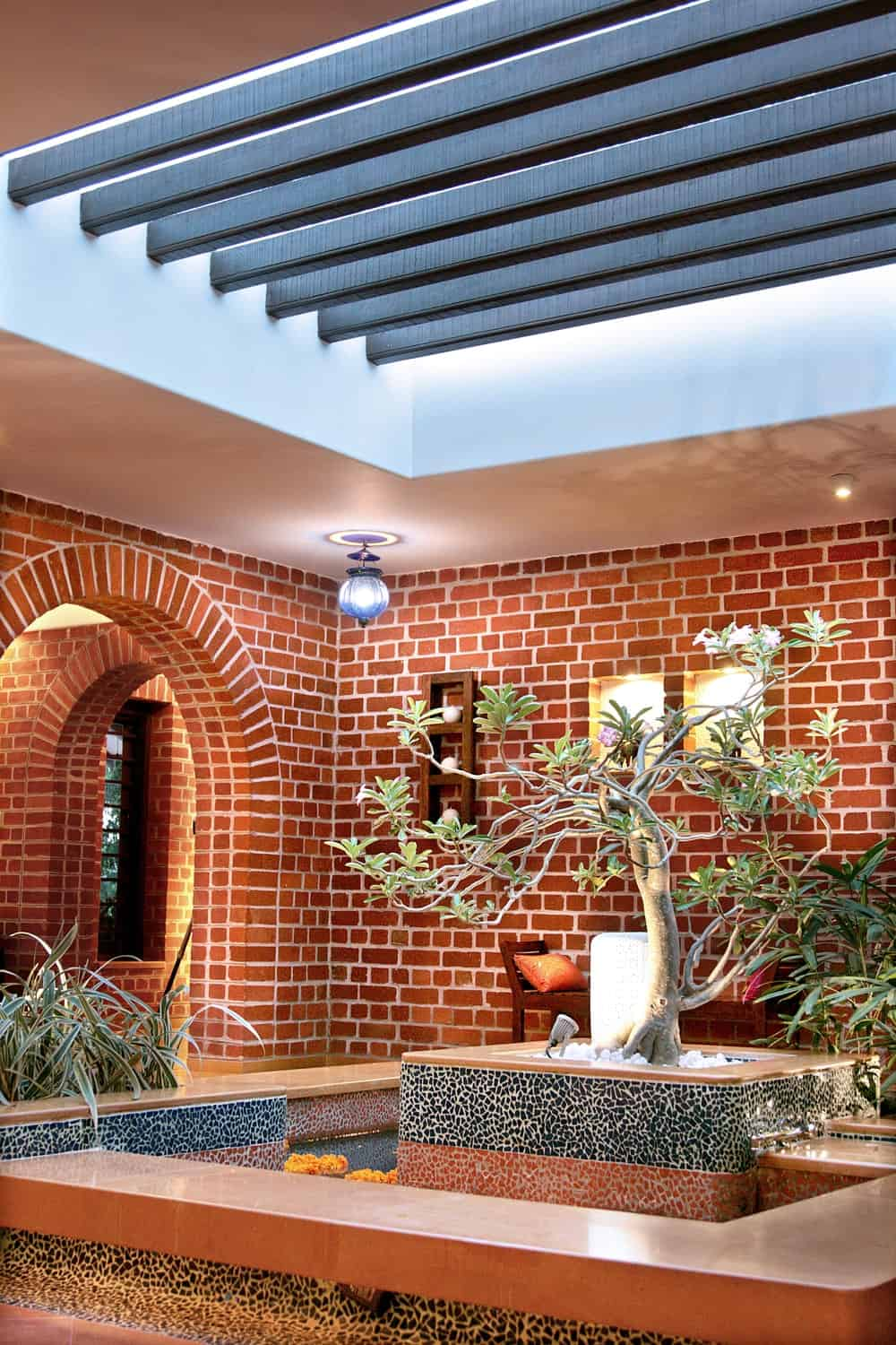 This area is also landscaped with a fountain adorned with a skylight that has trellises above.