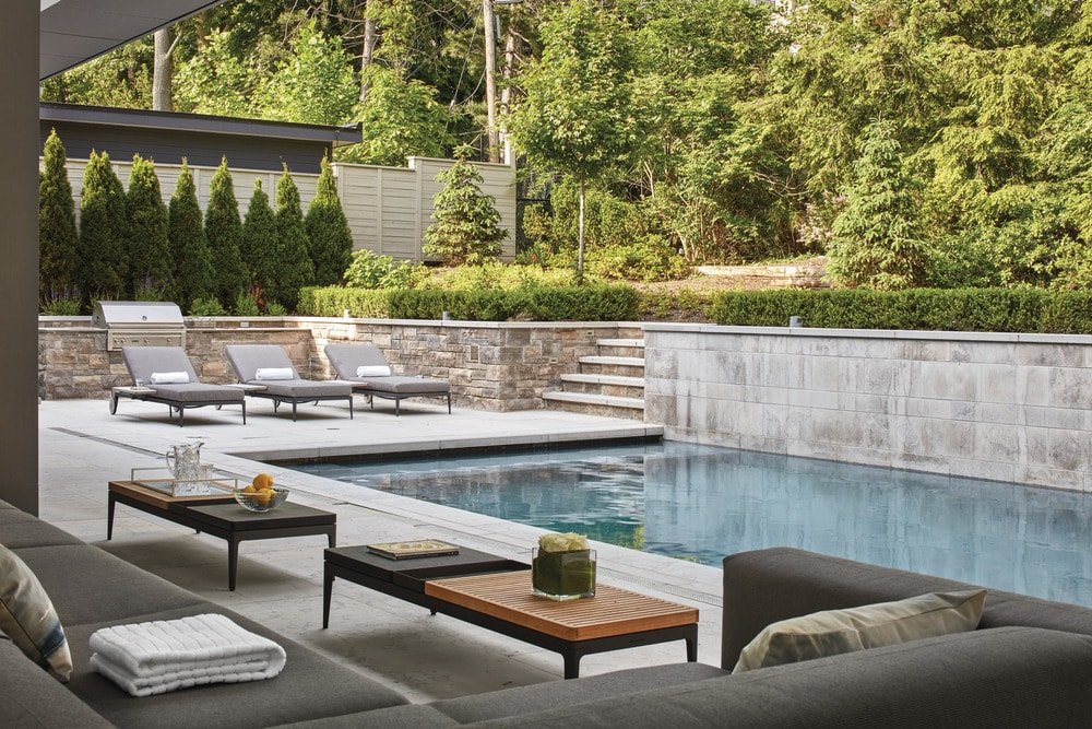 This is a look at the backyard pool from the vantage of the covered patio with a large outdoor L-shaped sectional sofa paired with coffee tables. There are also lounge chairs on the opposite side of the pool.