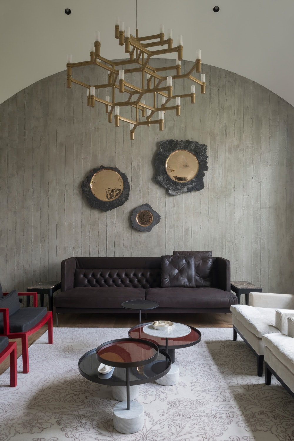 This is the living room that has a cove ceiling and a decorative lighting above the coffee tables that are surrounded by black and white sofas and armchairs.