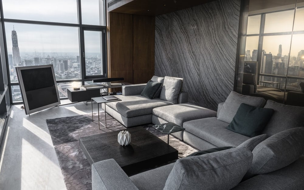 The large gray panel behind the sofa and the glass panel serve to separate the living room with the bedroom.