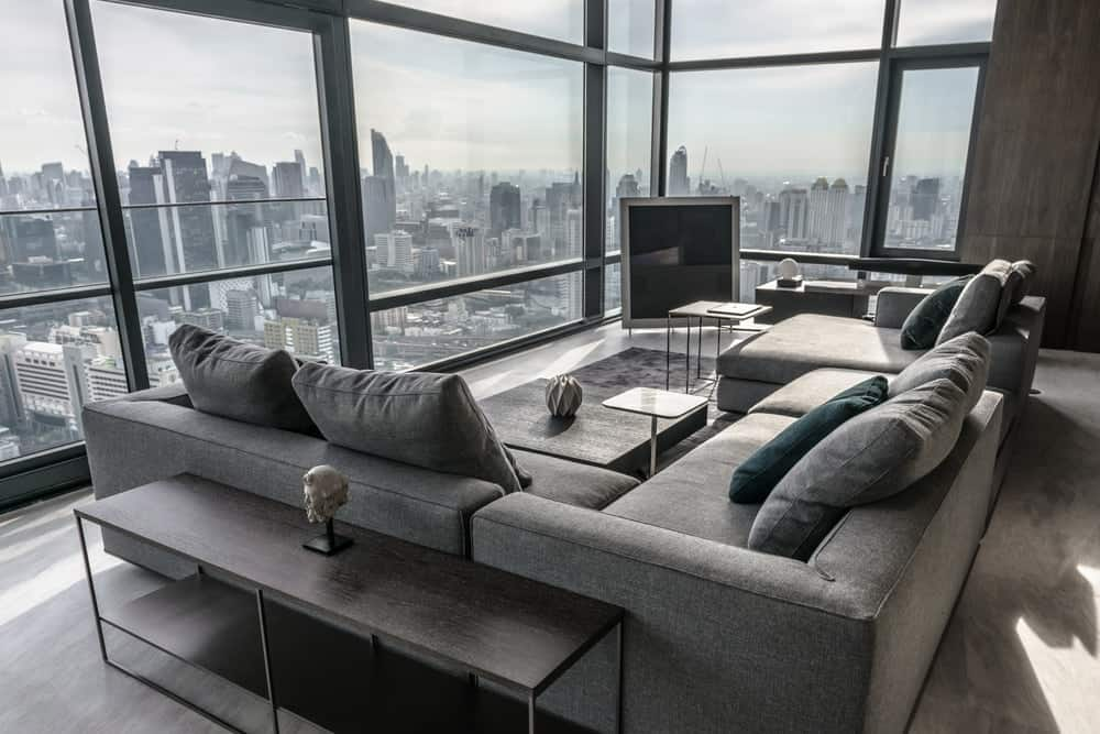 The large gray sectional sofa is paired with coffee tables and multiple side tables.