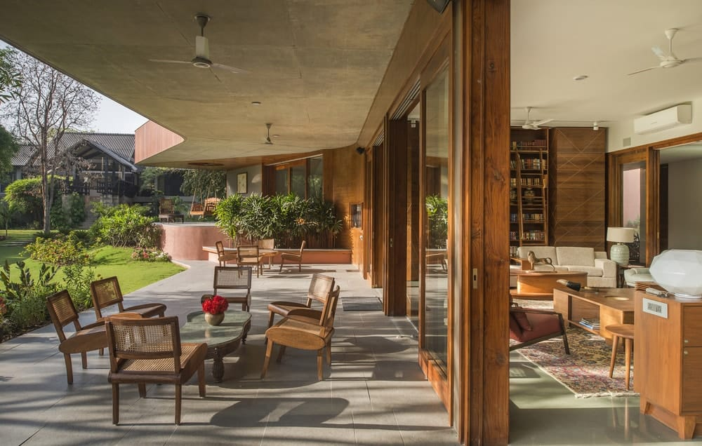 The large patio is separated from the large living room by glass walls with wooden frames.