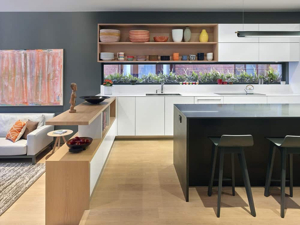 This is the kitchen with a large L-shaped peninsula and a dark kitchen island that stands out against the hardwood flooring and white cabinetry.