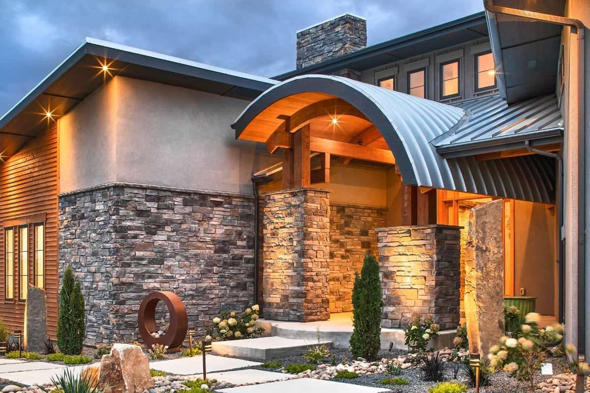 Home entry with concrete walkway, double columns, and an arched roof.