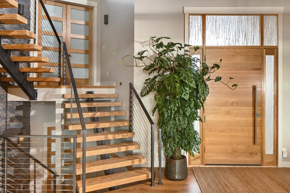 The foyer has a modern staircase, a tall potted plant, and a jute area rug.