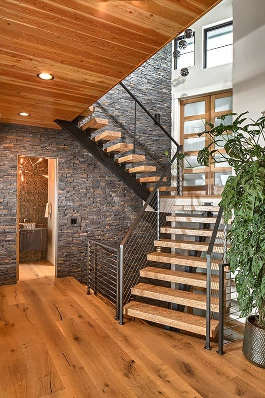 Next to the staircase is the powder room with striking stone walls.