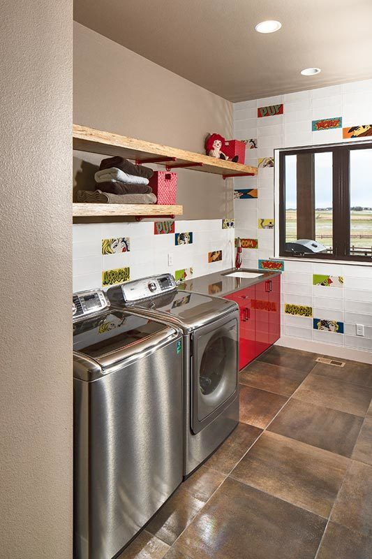 Laundry room with red high gloss cabinets, slate appliances, and wooden floating shelves.