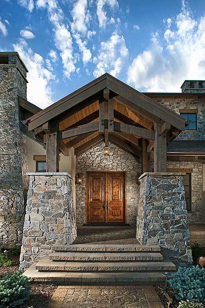 Home entry with a double front door, cathedral ceiling, and tapered columns that match the stone walls.