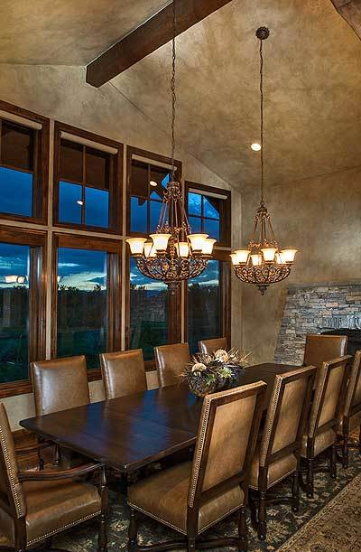 Dining area with leather chairs, a dark wood dining table, and a pair of warm glass chandeliers.