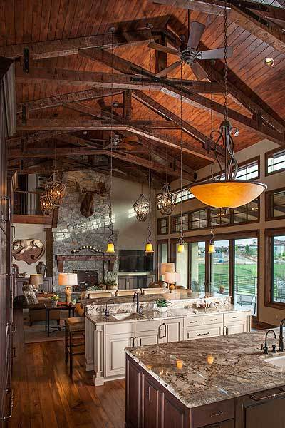 Open kitchen and living area with hardwood flooring and a vaulted ceiling framed with exposed wood beams.
