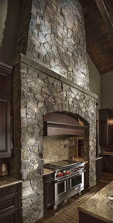 Stone cooking alcove with a stainless steel range paired with a bespoke vent hood.