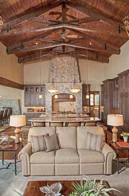 Living room with a beige sectional and wooden tables sitting on a cozy area rug.