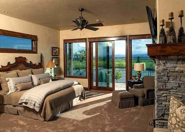 Primary bedroom with a wooden bed, a skirted lounge chair, and sliding glass doors that open to the covered deck.