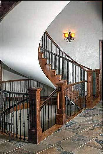 Winding staircase with wrought iron railings leading to the sleeping quarters and down the basement.
