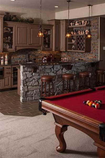 The recreation room is filled with a red billiards table and a wet bar well-lit by warm glass pendants.