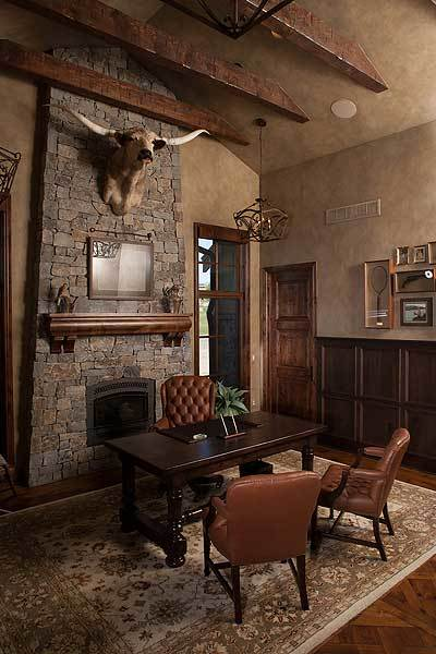 The study has tufted armchairs, a dark wood desk, a classic area rug, and a stone fireplace adorned with an animal head decor.