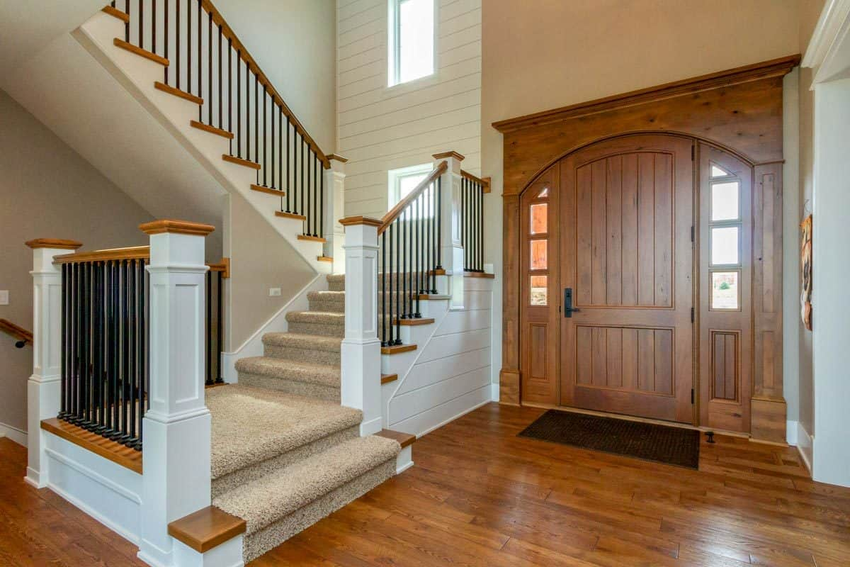 Foyer with an arched front door and a carpeted staircase framed with wrought iron railings.