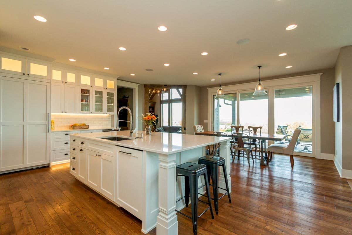 The eat-in kitchen features a wooden dining set and an immense island fitted with a sink.