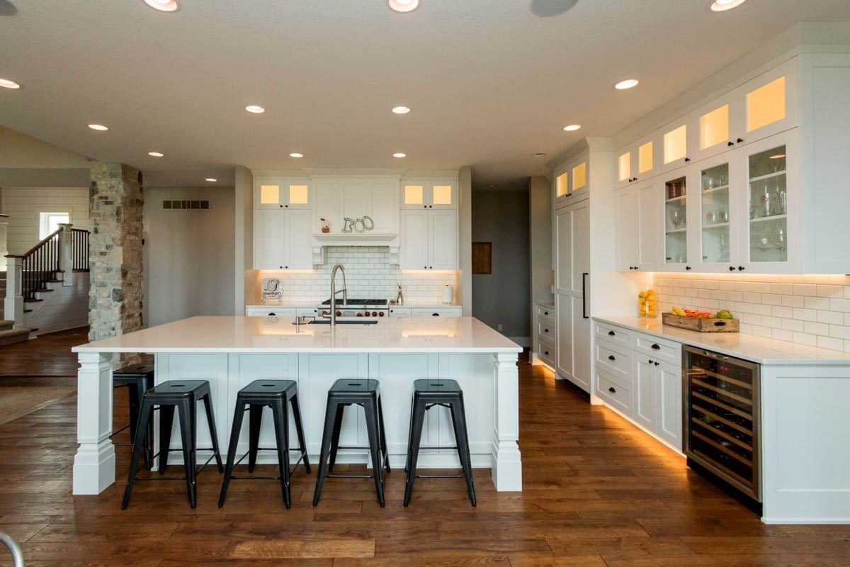 The kitchen is filled with white cabinetry, subway tile backsplash, a center island, and a built-in wine fridge.