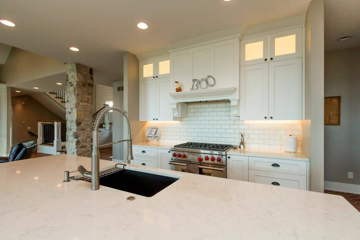 A closer look at the marble top island shows the undermount sink and a pull-down sprayer.
