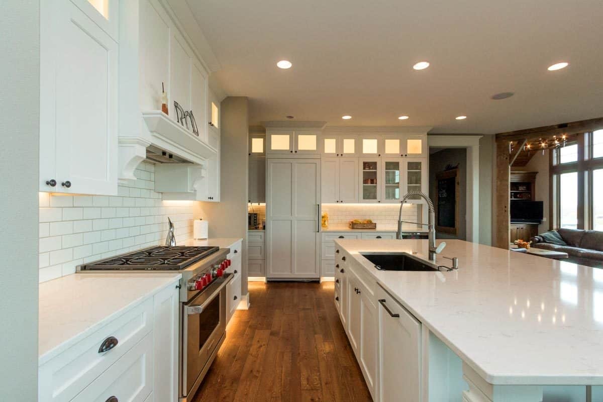 The wide plank flooring creates a cozy and contrasting look at the white kitchen.