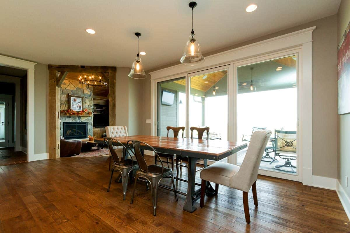 Dining area with mismatched chairs, a rectangular dining table, and glass dome pendants.