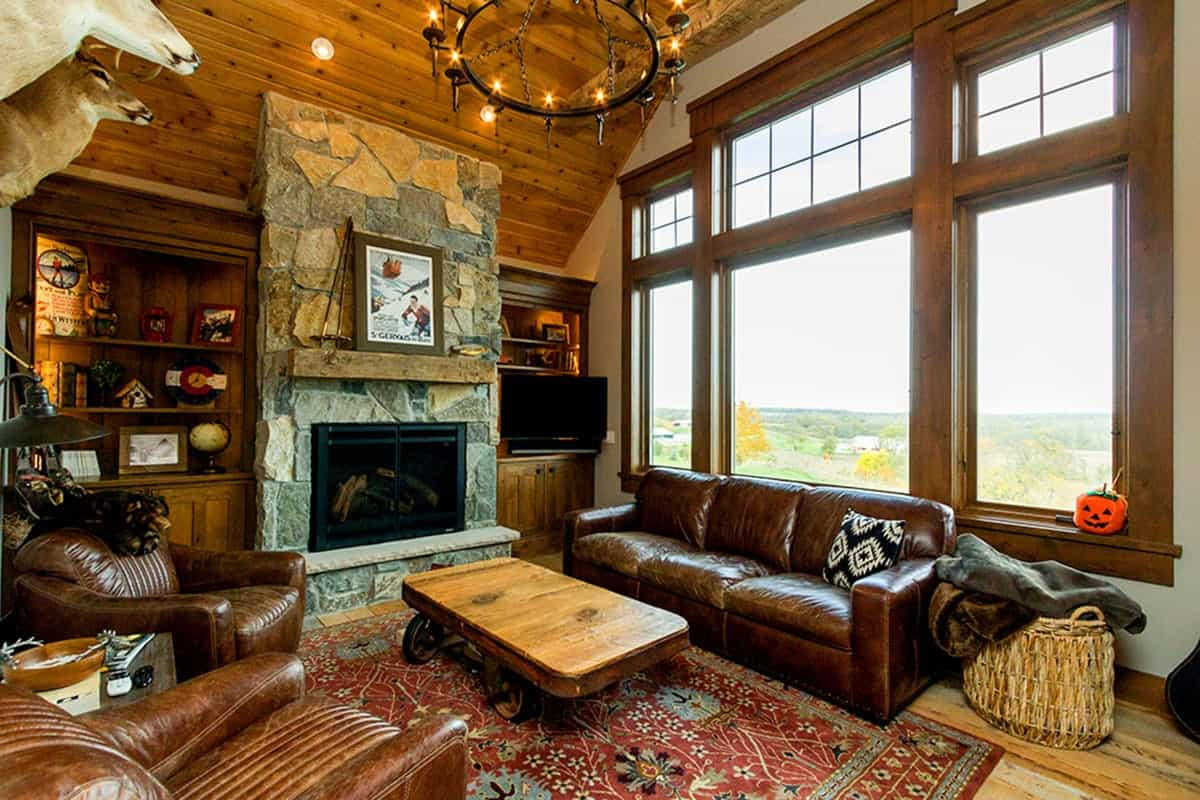 Hearth room with brown leather seats, stone fireplace, red floral rug, and a wooden coffee table with wheels.