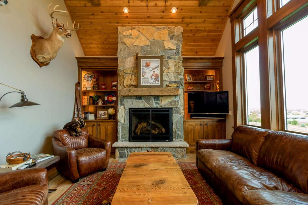 The hearth room is decorated with an antler head and a framed artwork that sits on the rustic mantel.