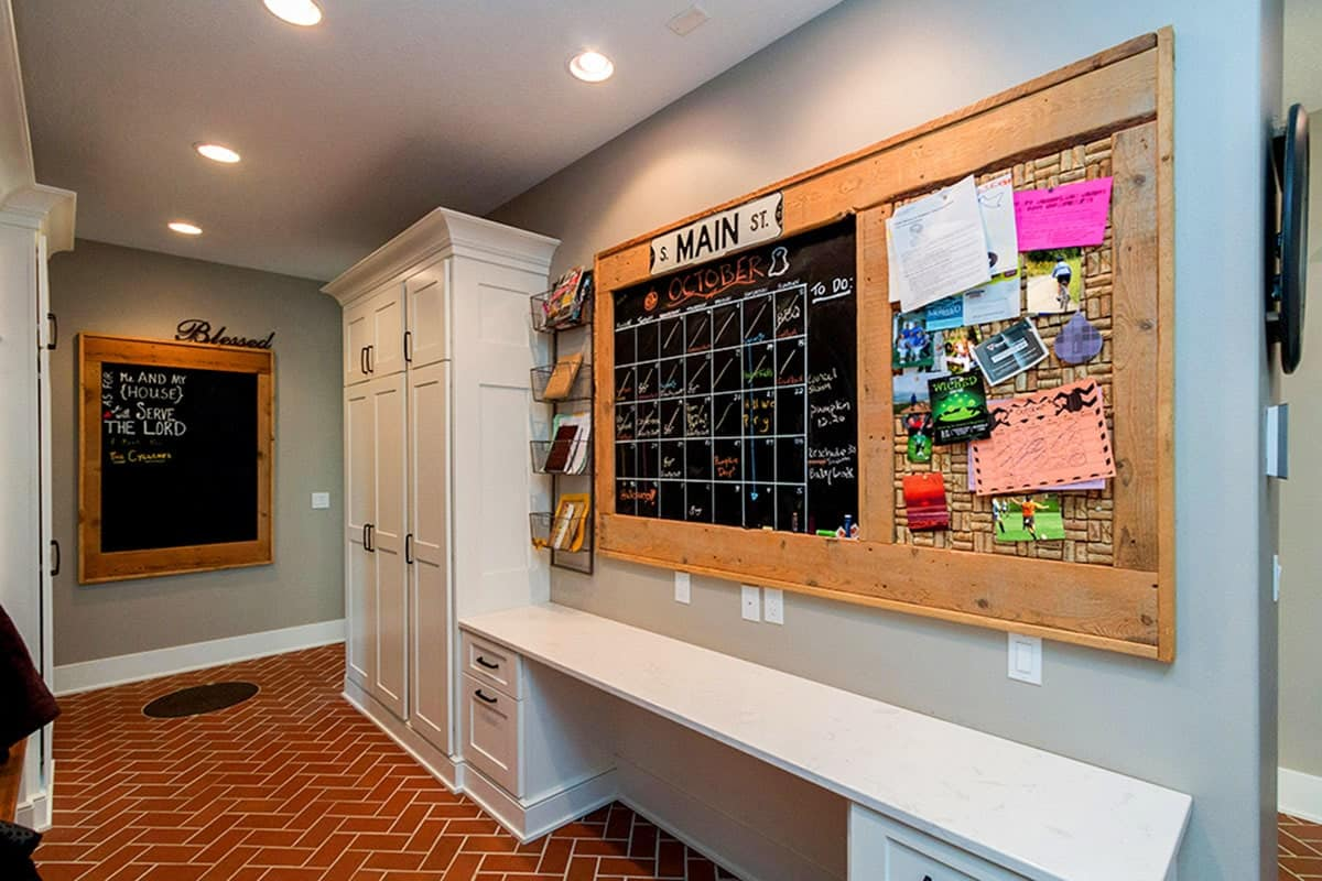 The mudroom has white lockers, a built-in seat, large cork and blackboards, storage shelves, and a red herringbone tile flooring.