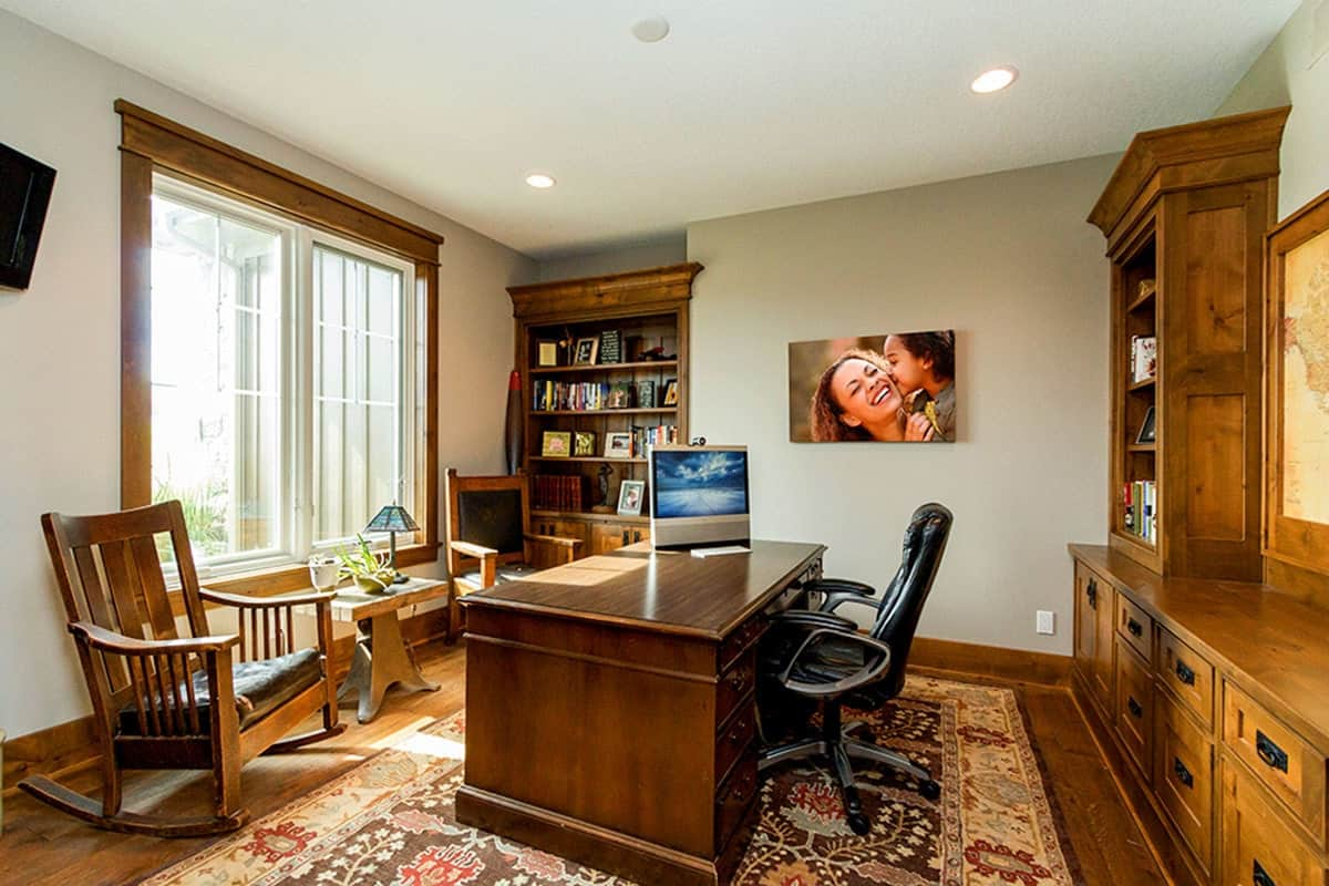 Study with leather and wooden chairs, built-in cabinets, natural wood desk, and a bordered floral rug.