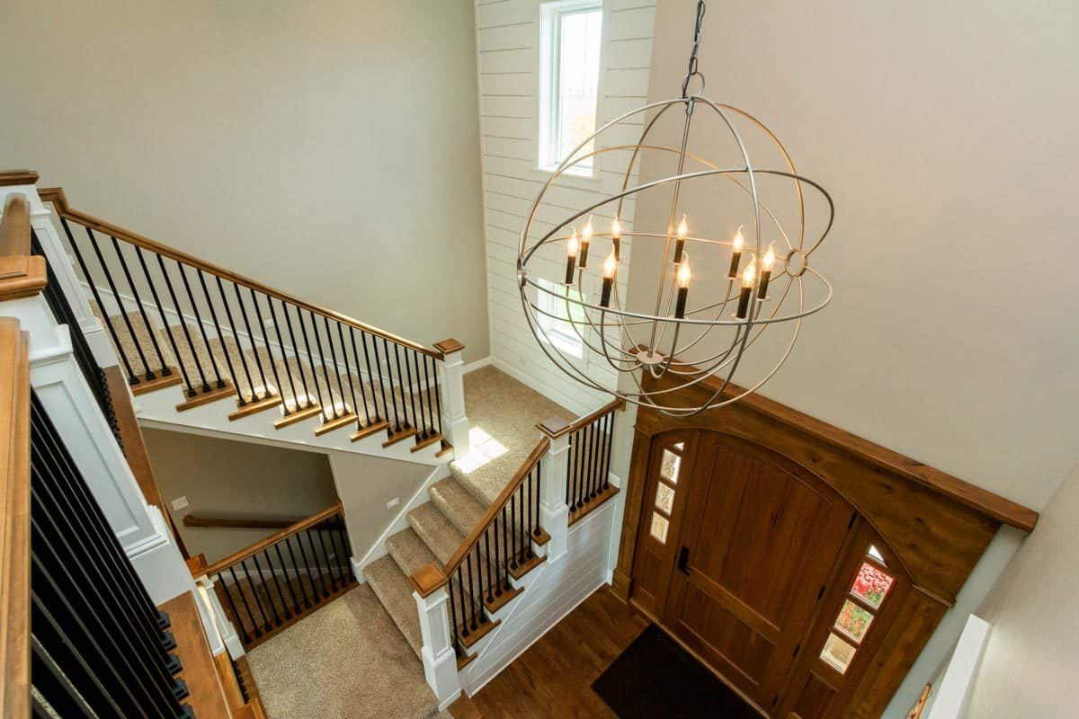 A spherical chandelier hanging from the two-story ceiling brightens the foyer.
