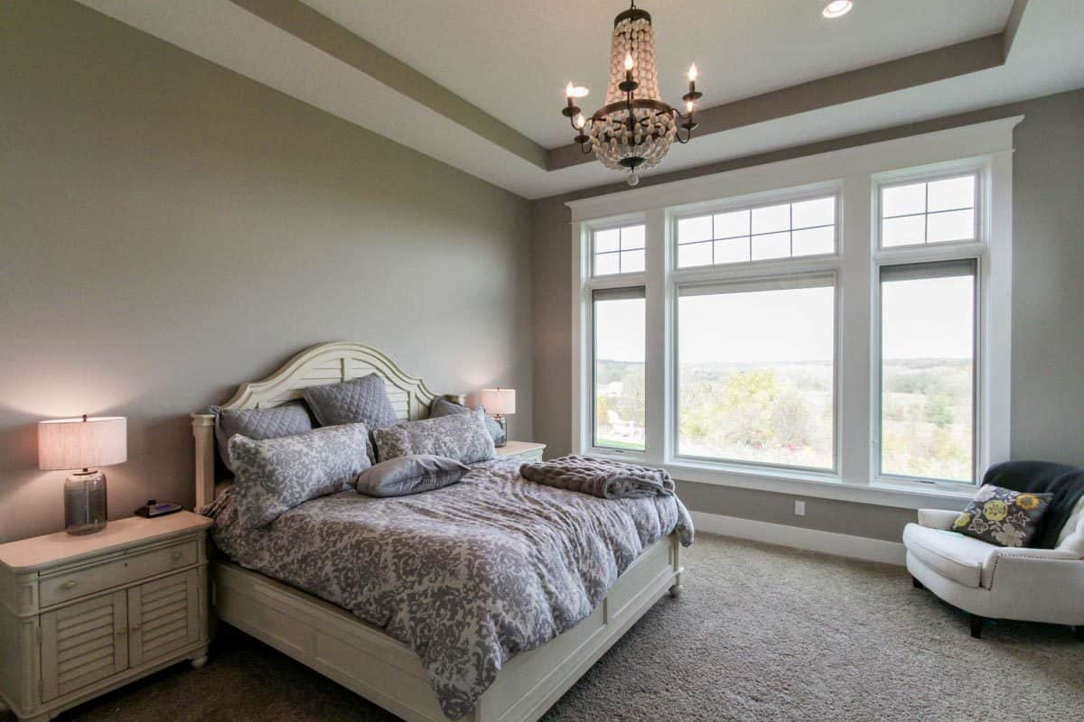 Primary bedroom with a tray ceiling, white furnishings, carpet flooring, three-panel windows, and a beaded chandelier.