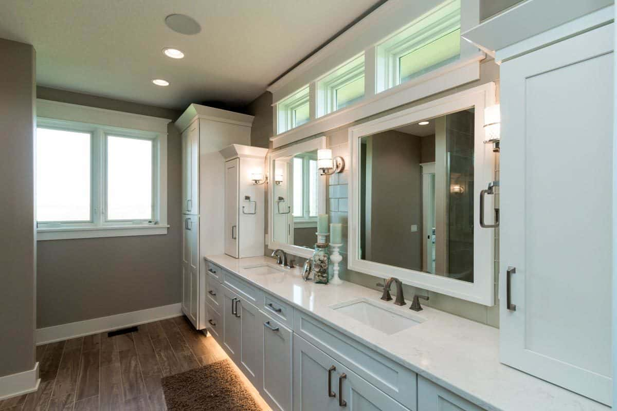 The primary bathroom features a large dual sink vanity with marble countertops, white framed mirrors, glass sconces, and brass fixtures.