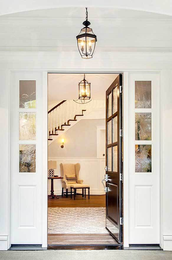A black front door opens to the foyer that's well-lit by warm glass pendant and sconce.