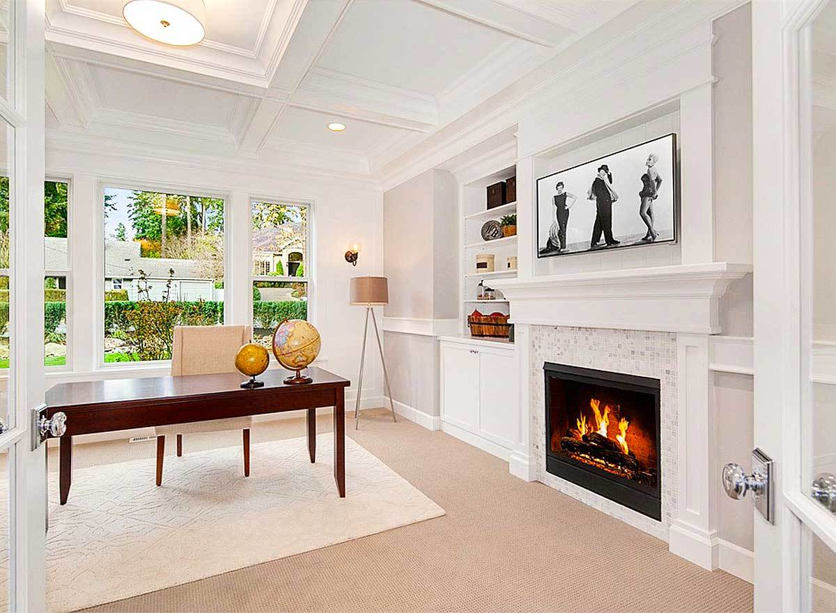 The study has a coffered ceiling, a modern fireplace, and a wooden desk paired with a beige upholstered chair.