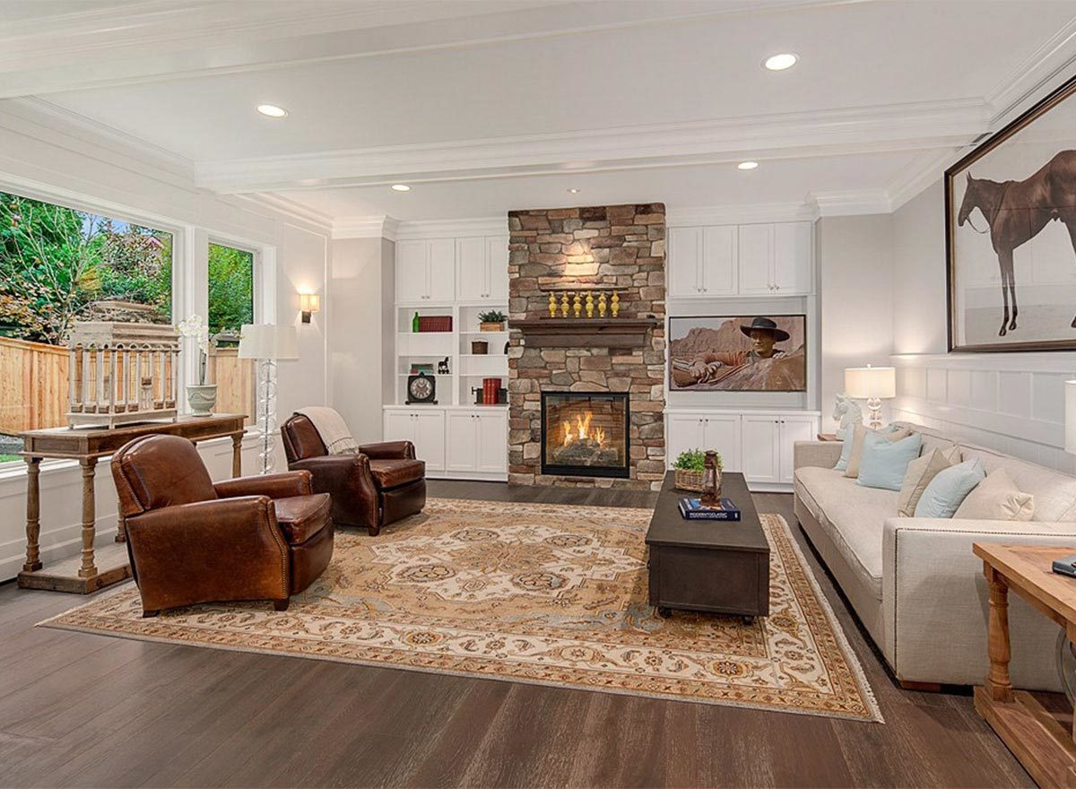 Living room with a beige sofa, leather sectionals, wooden tables, and a stone fireplace flanked by white built-ins.