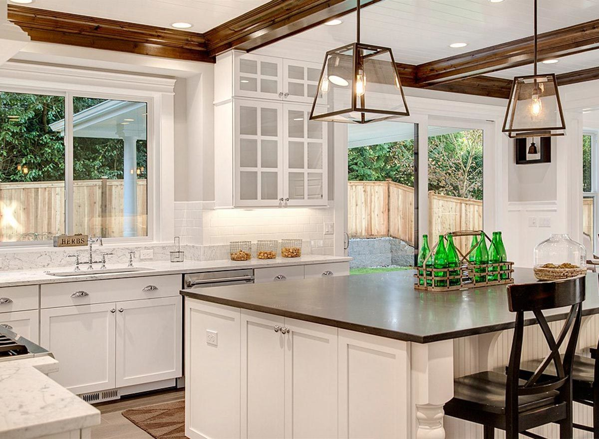 Kitchen with white and glass front cabinets, a breakfast island, and white marble countertops.