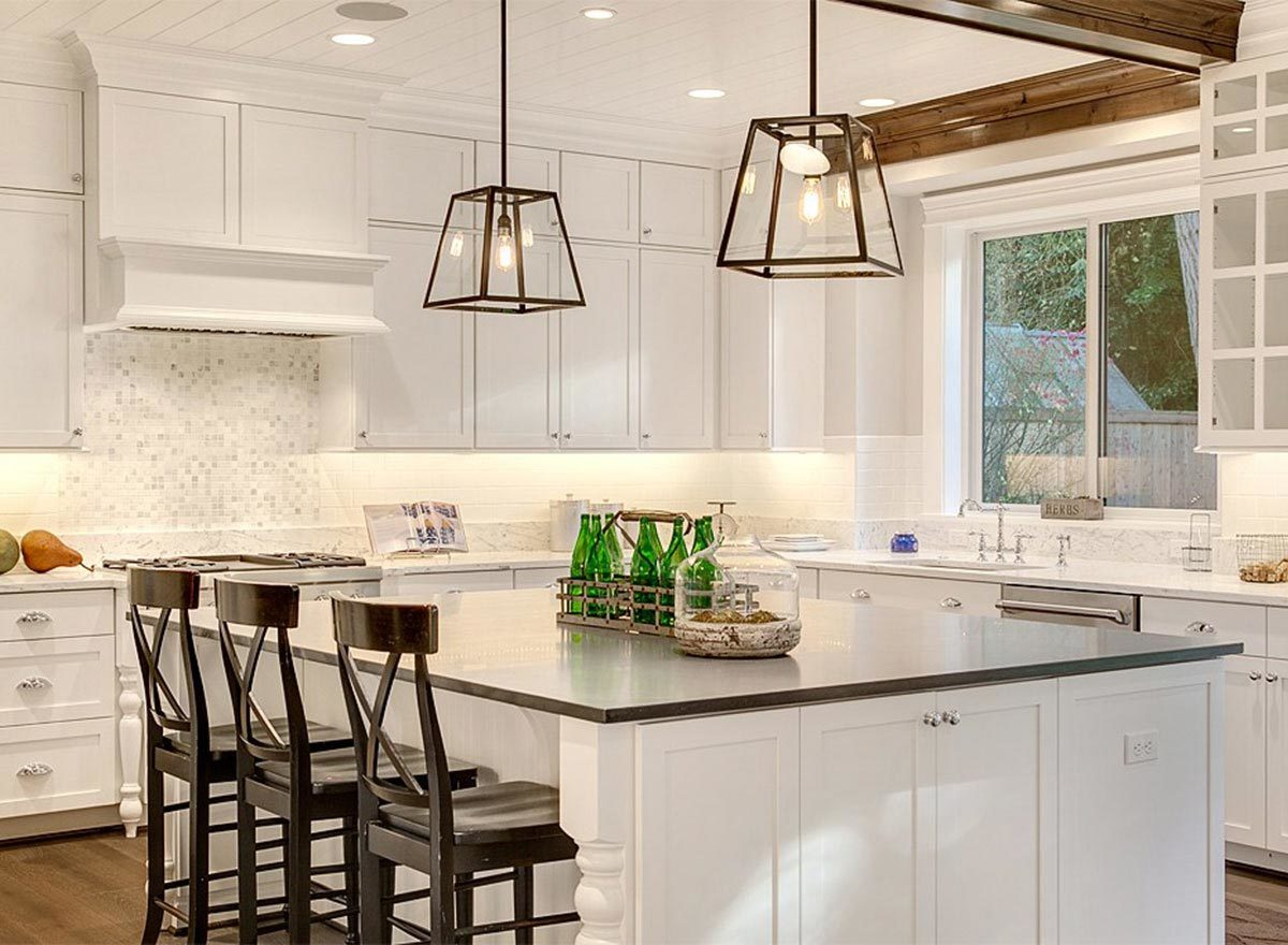 Black counter chairs and a pair of glass pendants complement the large center island.